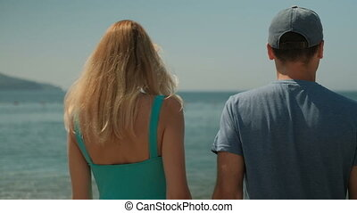 Young couple walking along beach on sunny afternoon outdoors.