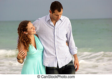 young couple walking along bonita beach in florida at the gulf of mexico having a discussion with waves crashing behind them. Woman is smiling and looking up at her man.