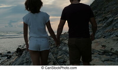 Young couple walking along coast in summer evening outdoor.