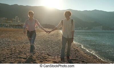 Young couple walking along seashore in summer day.