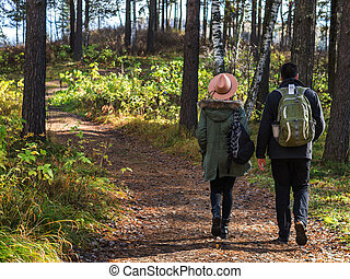 Young couple walking along the trail in the park on a sunny autumn day.