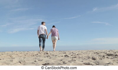 Young couple walking and talking together on the beach