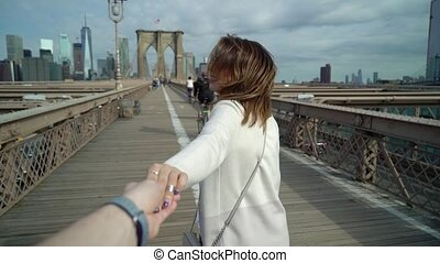 Young couple walking at Brooklyn bridge in New York