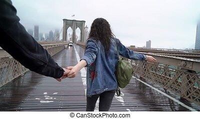 Young couple walking at Brooklyn bridge