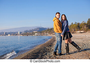 Young couple walking at the beach on a sunny winter day