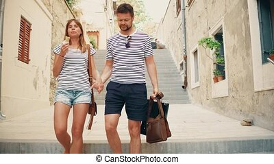 Young couple walking down pedestrian Mediterranean town street on vacation