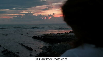 Young couple walking in evening on rocks near shore against a red sunset.