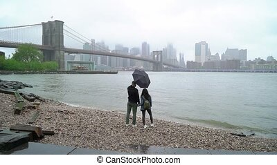 Young couple walking in New York at rain