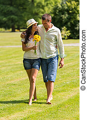 Young couple walking in park barefoot