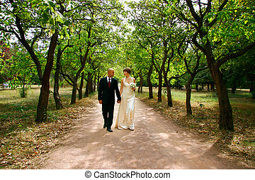 young couple walking in park on their wedding day
