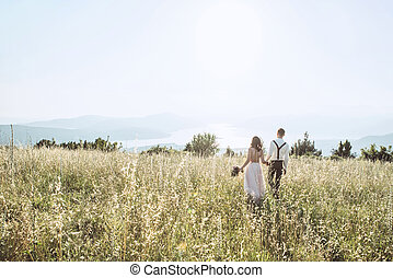 Young couple walking in the field.