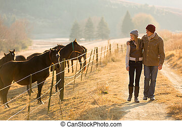 young couple walking in the horse farm - young romantic ...