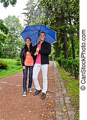 Young couple walking in the park under umbrella