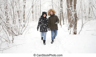 Young couple walking in the snowy forest