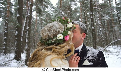 Young couple walking in winter forest holding hands and embracing in slow motion
