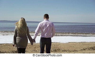 Young couple walking on a beach at autumn