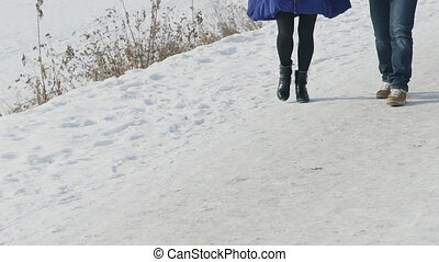 Young couple walking on bank of frozen river in snowy winter outdoors