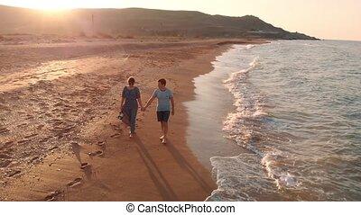 Young couple walking on beach - Young happy couple walking...