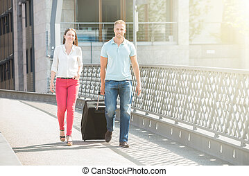 Young Couple Walking On Bridge With Luggage