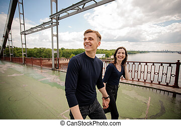 Young couple walking on bridge