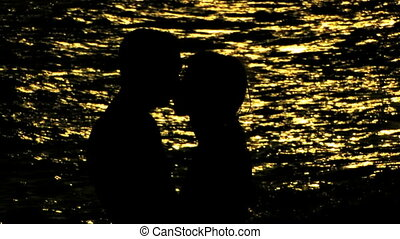 young couple walking on the beach - young couple kissing on...