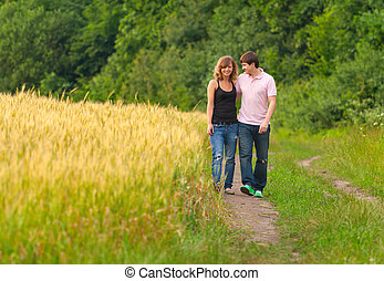 Young couple walking on the road in a field of wheat