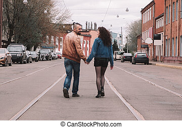 young couple walking on the road in a small town.