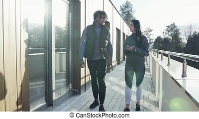 Young couple walking outdoors on terrace, restingg after doing exercise.