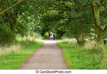 young couple walking their dog along a country path