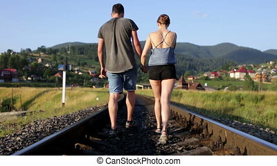Young couple walking together on railroad in mountains