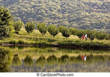 young couple walks along the lake shore