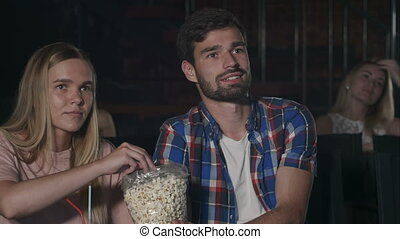 Young couple watching a movie at the cinema. Close up....