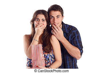 Young couple watching a scary movie and eating popcorn.