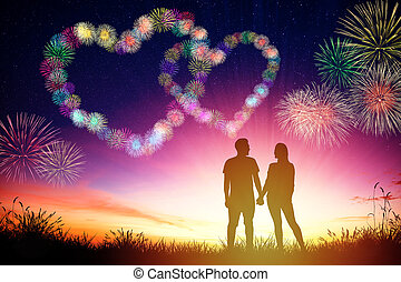 young couple watching heart shape fireworks on hill