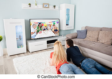 Young Couple Watching Movie On Television