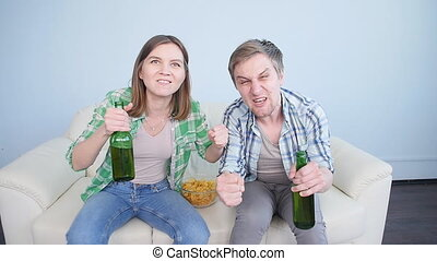 Young couple watching sports on TV at home