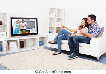 Young Couple Watching Television - Young Couple Sitting On...