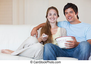 Young couple watching television while eating popcorn