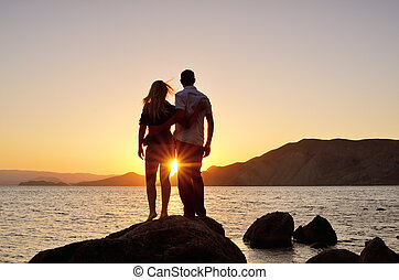 Young couple watching the sun by the sea