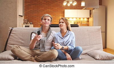 Young Couple Watching TV on the Sofa in the Living Room.