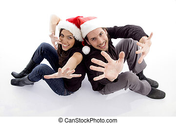 young couple wearing christmas hat with hand gesture on an...