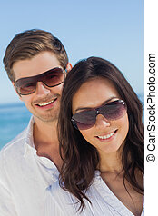 Young couple wearing sunglasses and smiling at camera at...