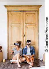 Young couple wir VR glasses moving in new house.