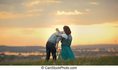 Young couple with a child dancing and having fun in nature, sunset
