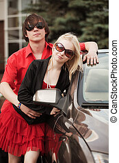 Young couple with a convertible car