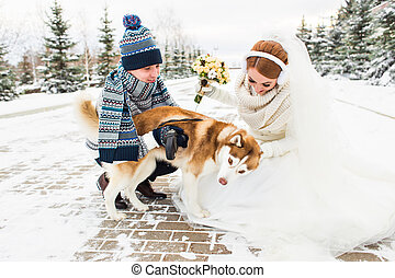Young couple with a dog on winter walk