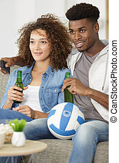 young couple with beer looking at tv