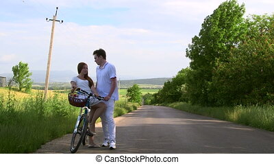 Young couple with bicycle and basket on country road