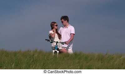 Young couple with bicycle in wheat field talking together