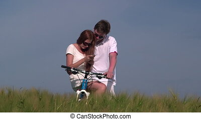 Young couple with bicycle takes a selfie in wheat field